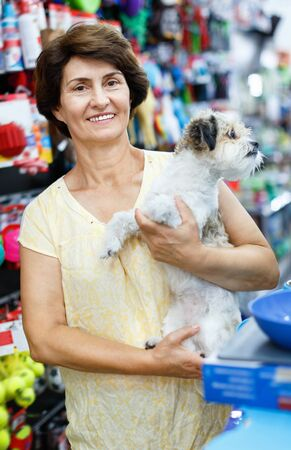Portrait of happy glad cheerful elderly woman visiting pet supplies store with her cute puppy of havanese