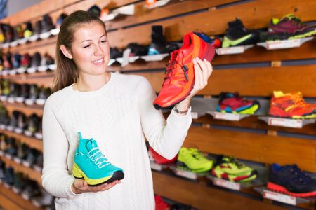 Positive athletic woman chooses sports footwear in specialty store Stockfoto