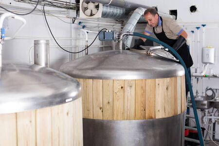 Brewer is controls the brewing process near reservoir with beer indoor. Stockfoto