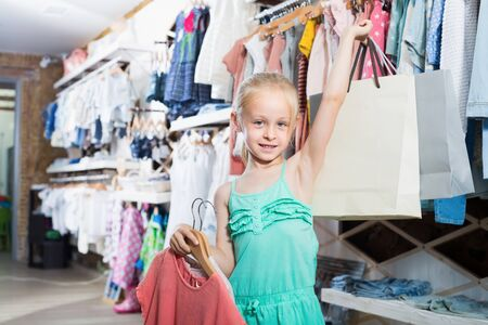 Hapy girl holding shopping bags in children clothes boutique