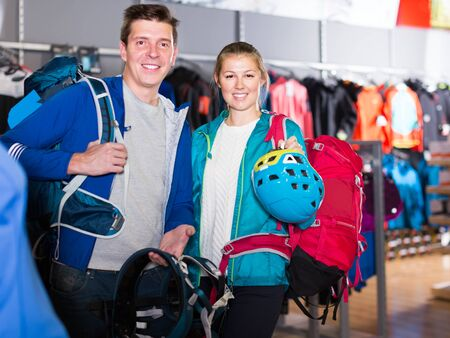smiling girl and guy select gear for hiking and camping from assortment in sports shop