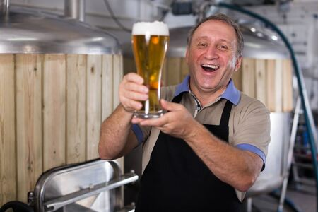 Adult brewer is standing with golden beer in glass in the fabric.