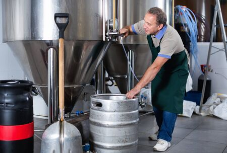Portrait of happy smiling brewer who is making beer and controls the process in the brew-house.