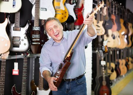 Smiling musician demonstrating an electric guitar in a music store Stock Photo