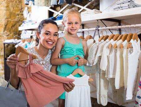 cheerful female with small girl choosing pink dress in kids apparel boutique Stockfoto - 130776599