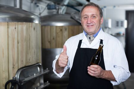 Adult brewer is standing with beer bottle in the fabric. Stockfoto