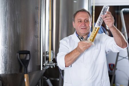 Man expert is analizying the quality of beer in flask in laboratory. Stockfoto