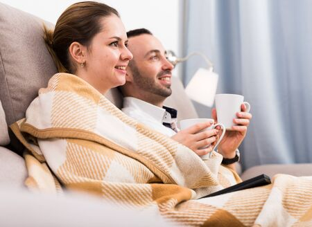 Man is watching TV with wife in time resting on sofa at home.