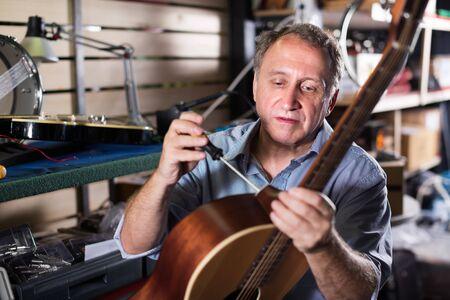 Adult man is repairing guitar because it is his hobby in workshop Stock Photo