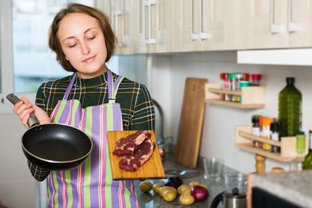 Young woman holding raw beef ready to cooking stew in home kitchen Stockfoto