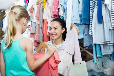 Young cheerful woman with small girl choosing pink clothes at kids apparel boutique