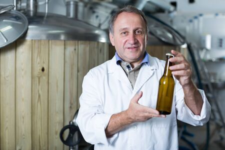Portrait of brewer who is standing with bottle for beer on his workplace in the brew-house.