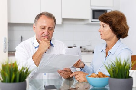 Worried mature couple  sitting at table with  financial documents in home kitchen Stock Photo