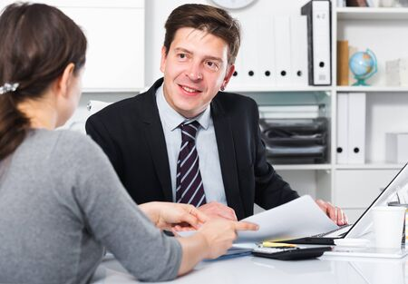 Cheerful businessman in suit talking about business with woman