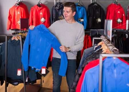 Young man chooses clothes in a sports shop
