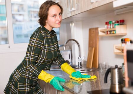 Young woman wearing protective yellow gloves cleaning kitchen surfaces Stock Photo