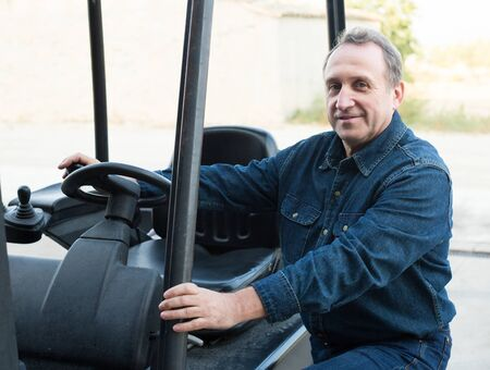 Smiling adult worker of winery goes driving loader Stockfoto