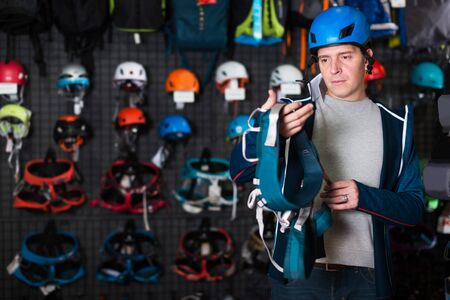 Young man chooses the gear for sports in store