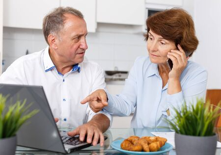 Portrait of smiling mature family couple with phone using laptop at kitchen table