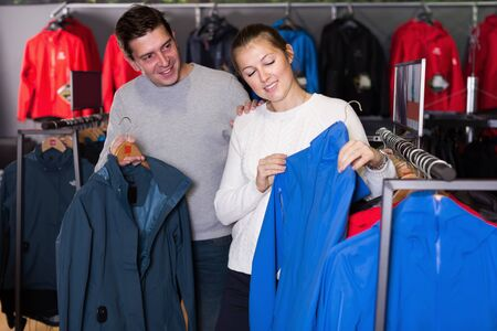 Smiling couple in sports shop to choose clothes or shoes
