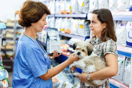 Elderly smiling female veterinarian recommending pet food to young woman visiting pet store with her puppy Archivio Fotografico