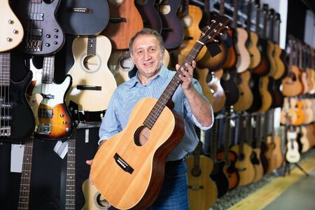 Adult glad cheerful positive guitarist is standing with acoustic guitar in music store. Stock Photo
