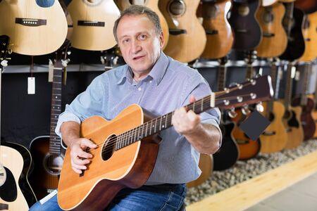 Porträt des erwachsenen Mannes spielt auf akustischer Gitarre und befriedigt es im Musikladen. Standard-Bild