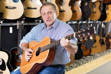 portrait of adult man is playing on acoustic guitar and satisfied it in music store.