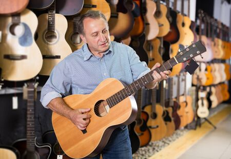 Man is playing on acoustic guitar and satisfied it in music store. Stock Photo