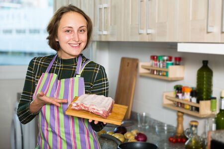 Portrait of young housewife in apron with raw pork ribs preparing food at home Stockfoto