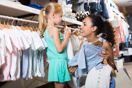Glad  adult mother with daughter buying kids clothes in blue color in shop Stockfoto - 130779268