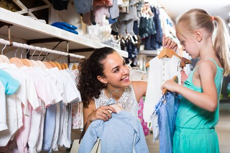 smiling young woman with little daughter selecting blue kids apparel in clothes store Stockfoto