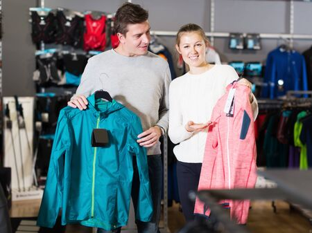 Young cheerful couple in sports store choosing sport clothes Stockfoto