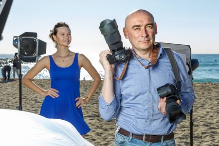 Portrait of successful photographer with his camera during professional photo shooting on sea coast