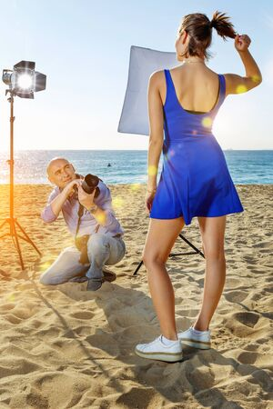 Photographer using professional camera and lighting equipment for taking pictures of young cheerful smiling woman in blue dress on sea coast Stockfoto