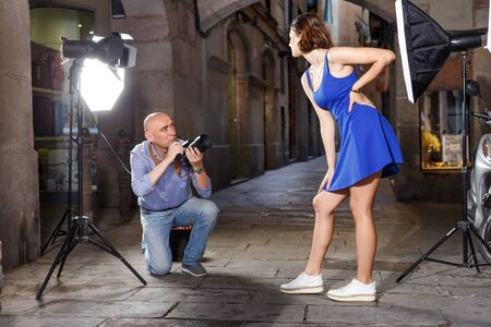 Professional photographer shooting young female model at an old city street