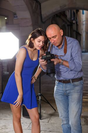 enthusiastic photographer and model discussing picture on camera display during photo session on city street