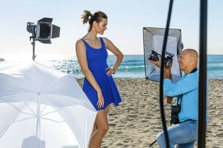 Professional photo shooting outdoors. cheerful female model posing to professional photographer on sunny beach Stockfoto