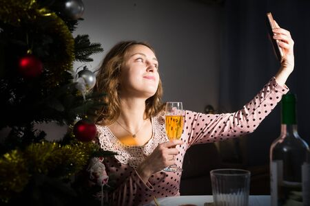 Pretty female is taking selfie with champagne in time celebration of New Year