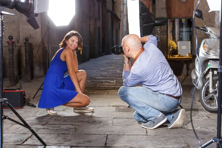 positive young woman in blue dress posing for professional photographer on old city street