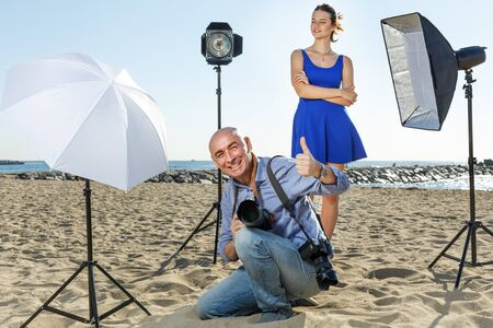 Portrait of excited male photographer sitting on sand with the his camera during professional photo shooting with female model on sea coast. Focus on man