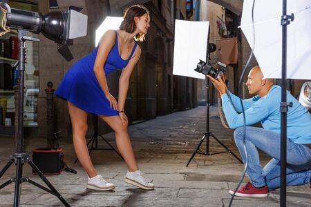 woman in blue dress posing for professional photographer on old city street