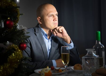 Portrait of tired lonely young man at New Year night at dining table