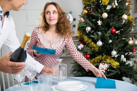 Husband and wife set the holiday table for Christmas Reklamní fotografie