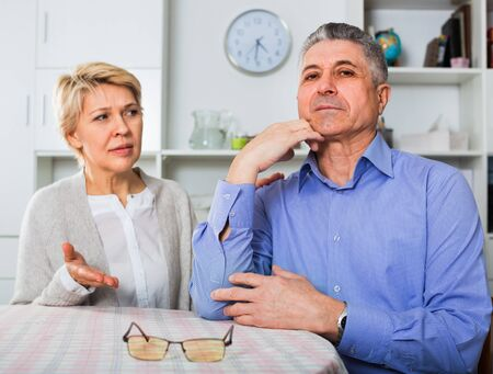 Elderly ordinary angry mature couple decide family matters and find out relationship in his house