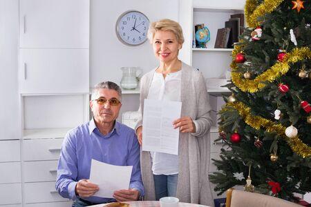 Una coppia sposata matura sorridente allegra discute il contratto a casa e firma documenti importanti important
