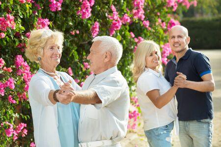 Mature friends dancing a walts at a green garden Standard-Bild - 130847254