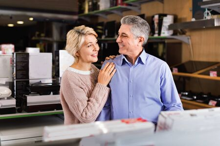 Adult glad positive smiling married couple in store looking at and choose home appliances for your home