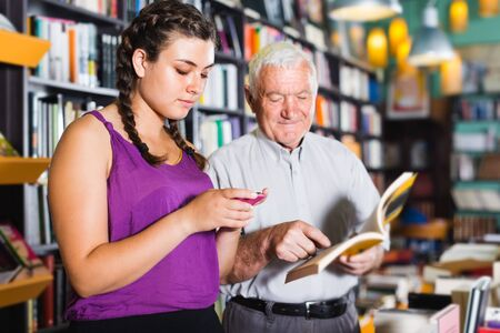 Mature man is choosing book while young female surfing in phone in bookstore.