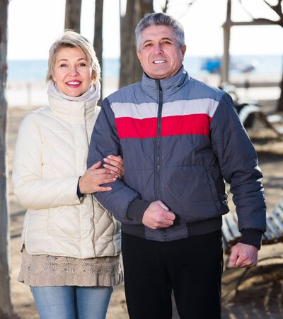 Glad husband and wife spend day together walking in park on seashore